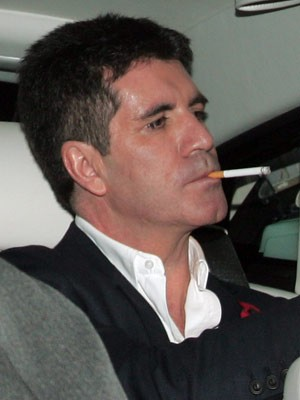 Simon Cowell smoking a cigarette (or weed)